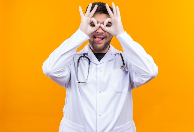 Młody przystojny lekarz ubrany w białą suknię medyczną białe rękawiczki medyczne i stetoskop zamykający oczy figlarnie robi okulary stojąc nad pomarańczową ścianą
