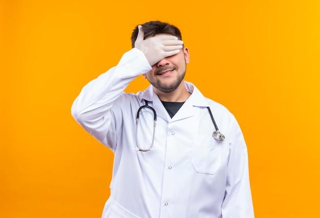 Młody przystojny lekarz ubrany w białą suknię medyczną białe rękawiczki medyczne i stetoskop zamykający oczy nieśmiało stojąc nad pomarańczową ścianą
