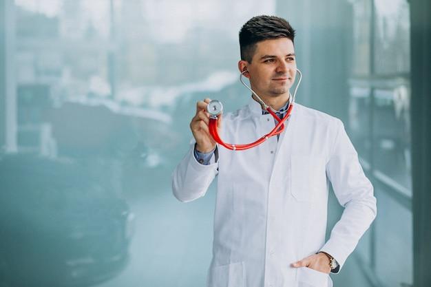 Młody przystojny lekarz w medycznej szacie z stetoskopem