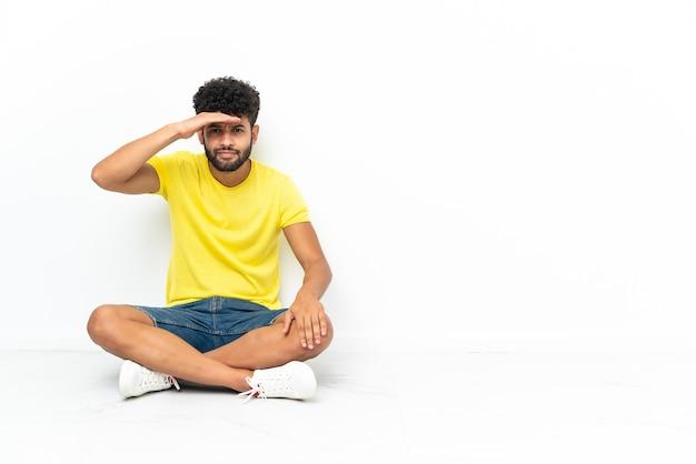 Młody przystojny marokański mężczyzna siedzi na podłodze na białym tle, patrząc daleko ręką, aby coś spojrzeć