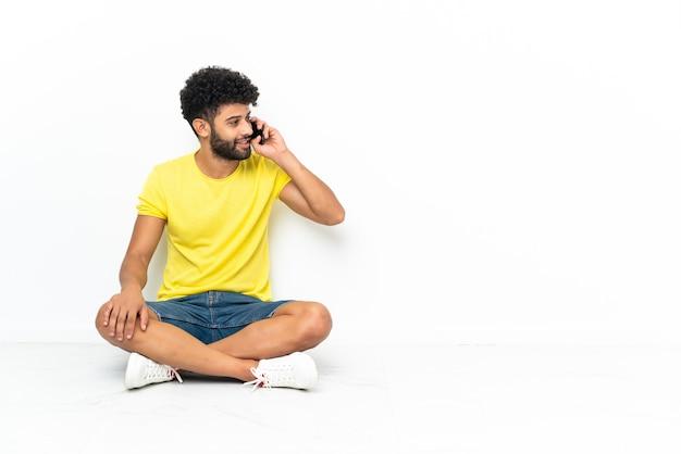 Młody przystojny marokański mężczyzna siedzi na podłodze na białym tle, prowadząc z kimś rozmowę z telefonem komórkowym