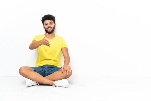 Młody przystojny marokański mężczyzna siedzi na podłodze na białym tle, ściskając ręce za zamknięcie dobrej oferty
