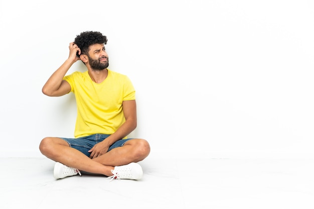 Młody przystojny marokański mężczyzna siedzi na podłodze nad izolowaną ścianą, mając wątpliwości i zdezorientowany wyraz twarzy