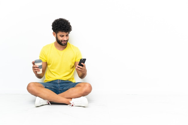 Młody przystojny marokański mężczyzna siedzi na podłodze nad odosobnioną ścianą, trzymając kawę na wynos i telefon komórkowy
