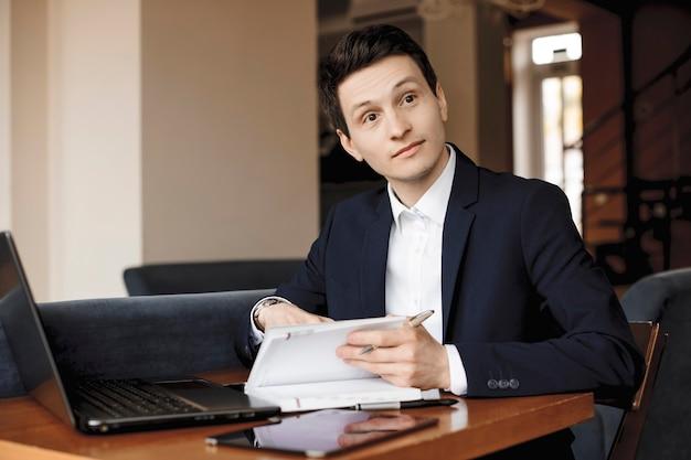 Młody przystojny menedżer przeprowadzający wywiady, patrząc zaskoczony, siedząc przy biurku.