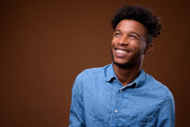 Młody przystojny mężczyzna afrykański myśli i uśmiecha się