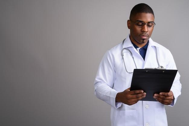 Młody przystojny mężczyzna afryki lekarz na szaro