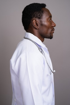 Młody przystojny mężczyzna afryki lekarz na szarym tle