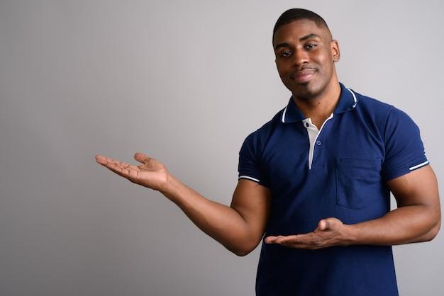 Młody przystojny mężczyzna afryki na sobie niebieską koszulkę polo na szaro