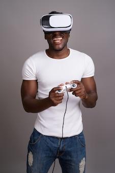 Młody przystojny mężczyzna afryki przy użyciu zestawu słuchawkowego wirtualnej rzeczywistości przeciwko