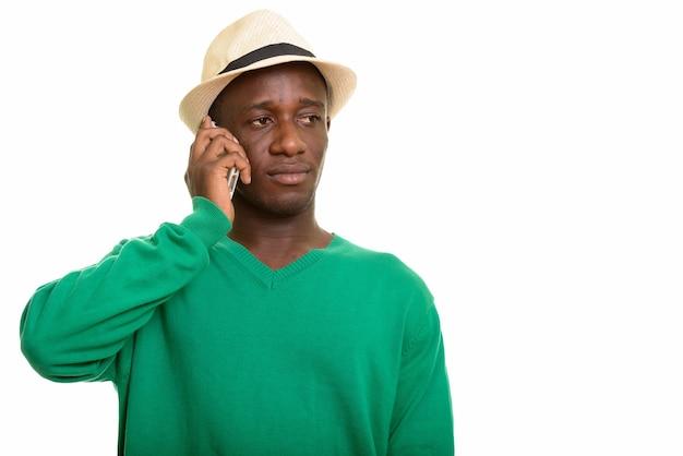 Młody przystojny mężczyzna afryki rozmawia przez telefon komórkowy podczas myślenia
