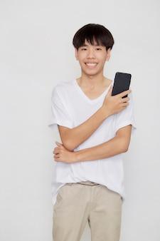 Młody przystojny mężczyzna azjatyckich posiadania telefonu komórkowego na tle białego studia