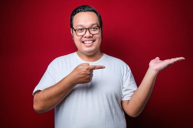 Młody przystojny mężczyzna azjatyckich sobie biały t-shirt na czerwonym tle z dużym uśmiechem na twarzy, wskazując palcem ręki na bok patrząc w kamerę.