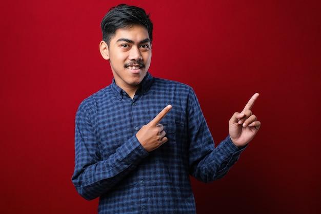 Młody przystojny mężczyzna azjatyckich sobie dorywczo koszulę na czerwonym tle z dużym uśmiechem na twarzy, wskazując palcem ręki na bok patrząc w kamerę.