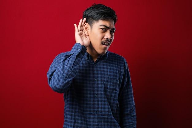 Młody przystojny mężczyzna azjatyckich ubrany dorywczo koszulę stojący na białym tle czerwony ciekawy z ręką na ucho słuchając przesłuchania plotek lub plotek. pojęcie głuchoty.