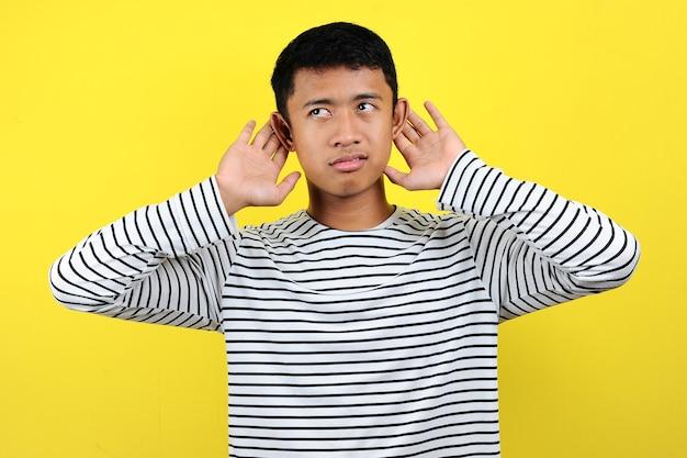 Młody przystojny mężczyzna azjatyckich ubrany w paski t-shirt, słuchając czegoś z ręką na uchu, słuchając przesłuchania plotek lub plotek. koncepcja głuchoty