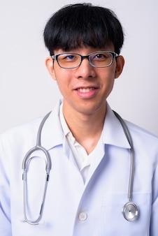 Młody przystojny mężczyzna azji lekarz przed białą ścianą