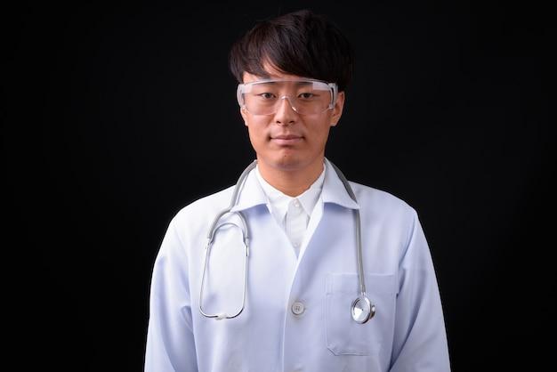 Młody przystojny mężczyzna azji lekarz w okularach ochronnych na czarno