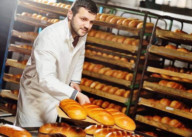 Młody przystojny mężczyzna baker w białym fartuchu wyciąga z pieca świeże pyszne różowe bochenki na tle fabryki chleba.