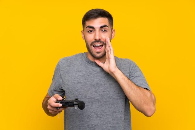 Młody przystojny mężczyzna bawić się z kontrolerem gier wideo nad odosobnioną kolor żółty ścianą z niespodzianką i zszokowanym wyrazem twarzy