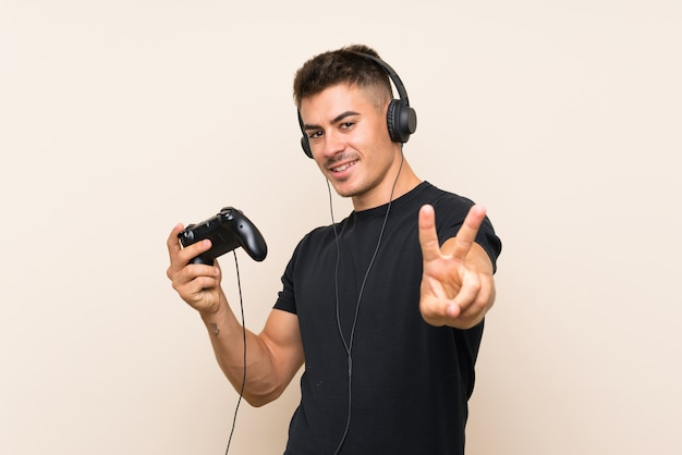 Młody przystojny mężczyzna bawić się z kontrolerem gier wideo uśmiecha się znak zwycięstwa i pokazuje