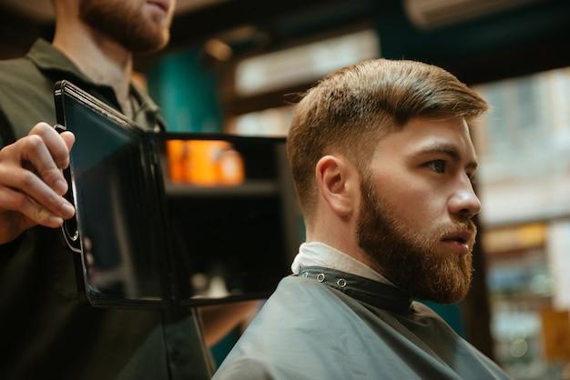 Młody przystojny mężczyzna coraz strzyżenie przez fryzjera siedząc w fotelu.