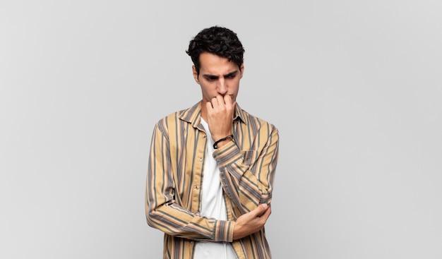 Młody przystojny mężczyzna czujący się poważnie, zamyślony i zatroskany, wpatrzony w bok z ręką przyciśniętą do brody