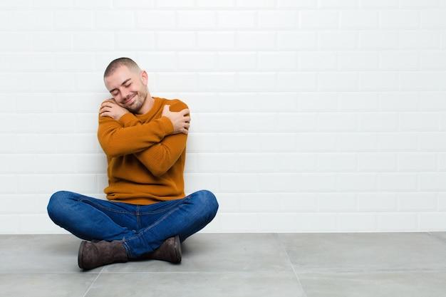 Młody przystojny mężczyzna czujący się zakochany, uśmiechnięty, przytulający się i przytulający, samotny, samolubny i egocentryczny, siedzący na podłodze
