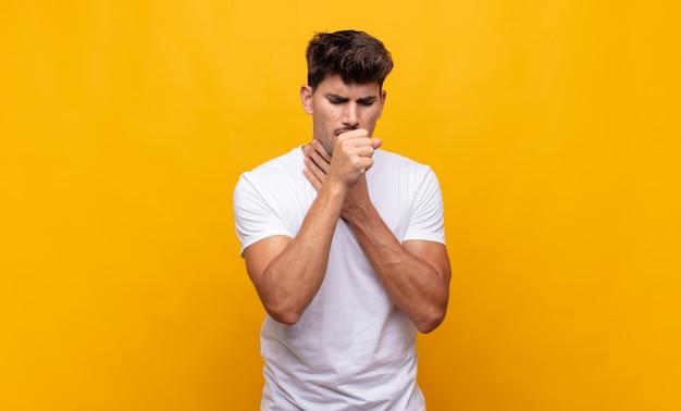 Młody przystojny mężczyzna czuje się chory z bólem gardła i objawami grypy, kaszle z zakrytymi ustami