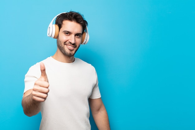 Młody przystojny mężczyzna czuje się dumny, beztroski, pewny siebie i szczęśliwy, uśmiechając się pozytywnie z kciukami w górę