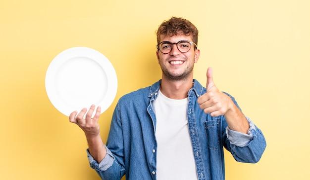 Młody przystojny mężczyzna czuje się dumny, uśmiechając się pozytywnie z kciukami do góry. koncepcja pustego naczynia