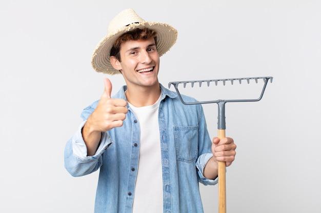Młody przystojny mężczyzna czuje się dumny, uśmiechając się pozytywnie z kciukami do góry. koncepcja rolnika