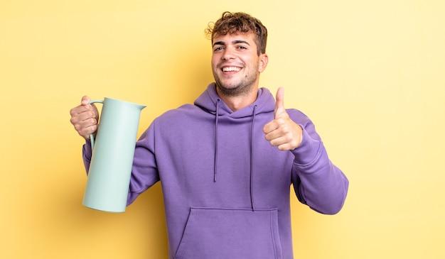 Młody przystojny mężczyzna czuje się dumny, uśmiechając się pozytywnie z kciukami do góry. koncepcja termosu
