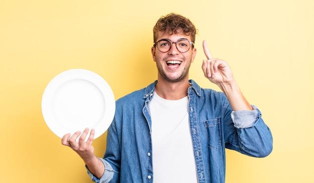 Młody przystojny mężczyzna czuje się jak szczęśliwy i podekscytowany geniusz po zrealizowaniu pomysłu. koncepcja pustego naczynia