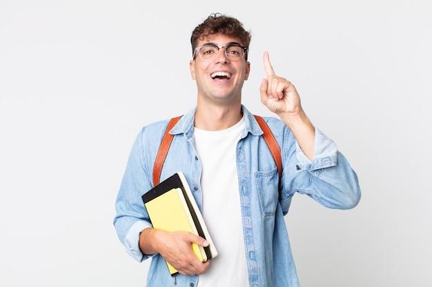 Młody przystojny mężczyzna czuje się jak szczęśliwy i podekscytowany geniusz po zrealizowaniu pomysłu. koncepcja studenta uniwersytetu