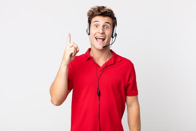 Młody przystojny mężczyzna czuje się jak szczęśliwy i podekscytowany geniusz po zrealizowaniu pomysłu. koncepcja telemarketera