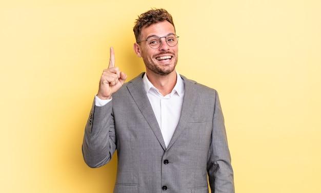 Młody przystojny mężczyzna czuje się jak szczęśliwy i podekscytowany geniusz po zrealizowaniu pomysłu. pomysł na biznes