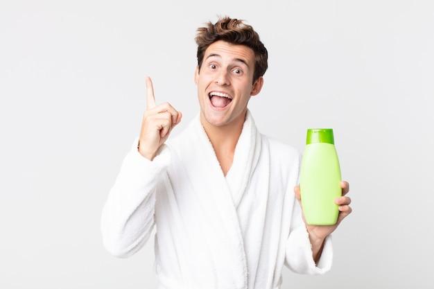 Młody przystojny mężczyzna czuje się jak szczęśliwy i podekscytowany geniusz po zrealizowaniu pomysłu ze szlafrokiem i trzymając butelkę szamponu