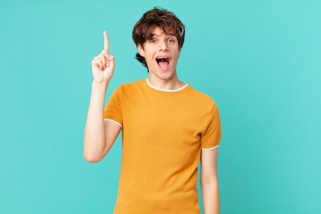 Młody przystojny mężczyzna czuje się jak szczęśliwy i podekscytowany geniusz po zrealizowaniu pomysłu