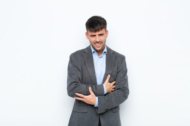 Młody przystojny mężczyzna czuje się niespokojny, chory, chory i nieszczęśliwy, cierpi na bolesny ból brzucha lub grypę na białej ścianie