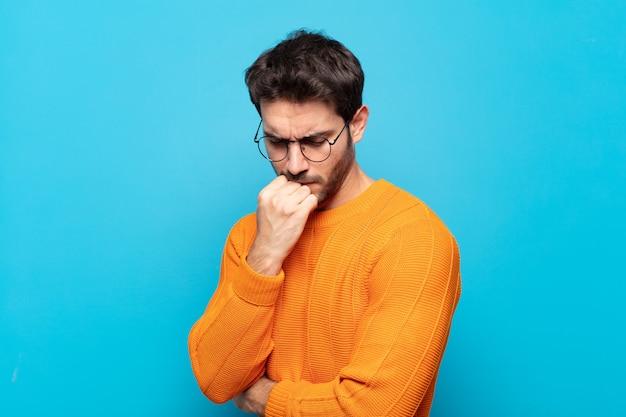 Młody przystojny mężczyzna czuje się poważny, zamyślony i zatroskany, wpatrując się w bok z dłonią przyciśniętą do podbródka