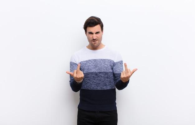 Młody przystojny mężczyzna czuje się prowokacyjnie, agresywnie i nieprzyzwoicie, machając środkowym palcem, z buntowniczym nastawieniem na białej ścianie