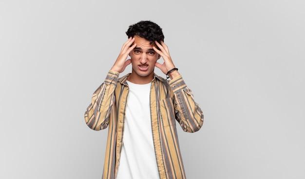 Młody przystojny mężczyzna czuje się przerażony i zszokowany, podnosząc ręce do głowy i panikując z powodu błędu