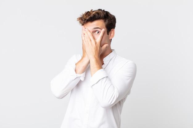 Młody przystojny mężczyzna czuje się przestraszony lub zawstydzony, zerka lub podgląda z oczami na wpół zakrytymi rękoma