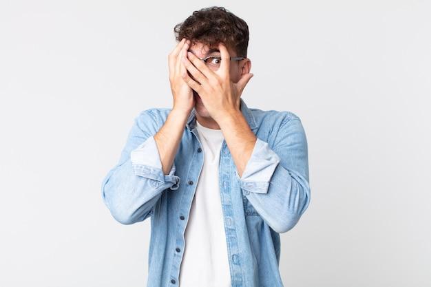 Młody przystojny mężczyzna czuje się przestraszony lub zawstydzony, zerka lub szpieguje z oczami na wpół zakrytymi rękami