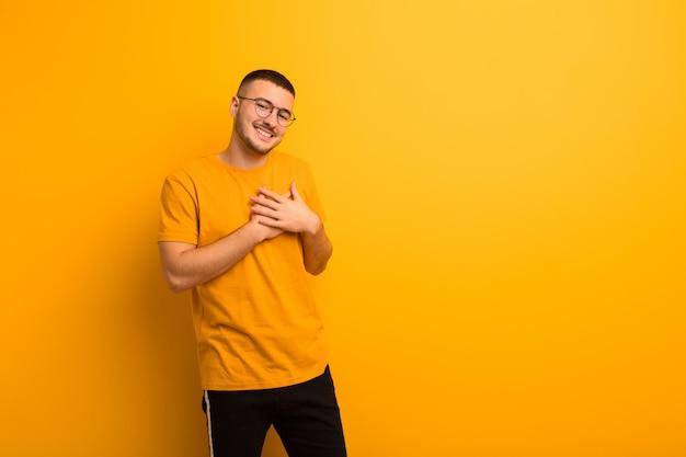 Młody przystojny mężczyzna czuje się romantyczny, szczęśliwy i zakochany, uśmiecha się radośnie i trzyma ręce blisko serca na płaskiej ścianie