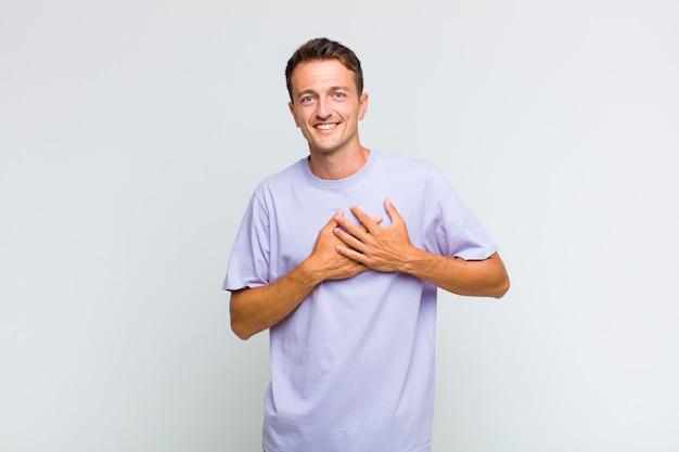 Młody przystojny mężczyzna czuje się romantyczny, szczęśliwy i zakochany, uśmiecha się radośnie i trzyma ręce blisko serca