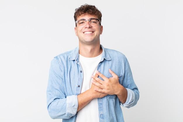 Młody przystojny mężczyzna czuje się romantyczny, szczęśliwy i zakochany, uśmiechając się radośnie i trzymając ręce blisko serca