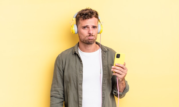 Młody przystojny mężczyzna czuje się smutny i jęczy z nieszczęśliwym spojrzeniem i płaczem w słuchawkach i koncepcji smartfona