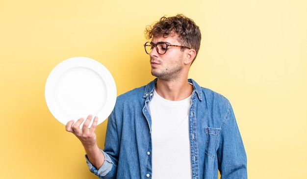 Młody przystojny mężczyzna czuje się smutny, zdenerwowany lub zły i patrząc w bok. koncepcja pustego naczynia